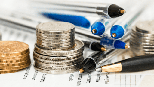 #reporting Pens and coins piled up on financial reports and data
