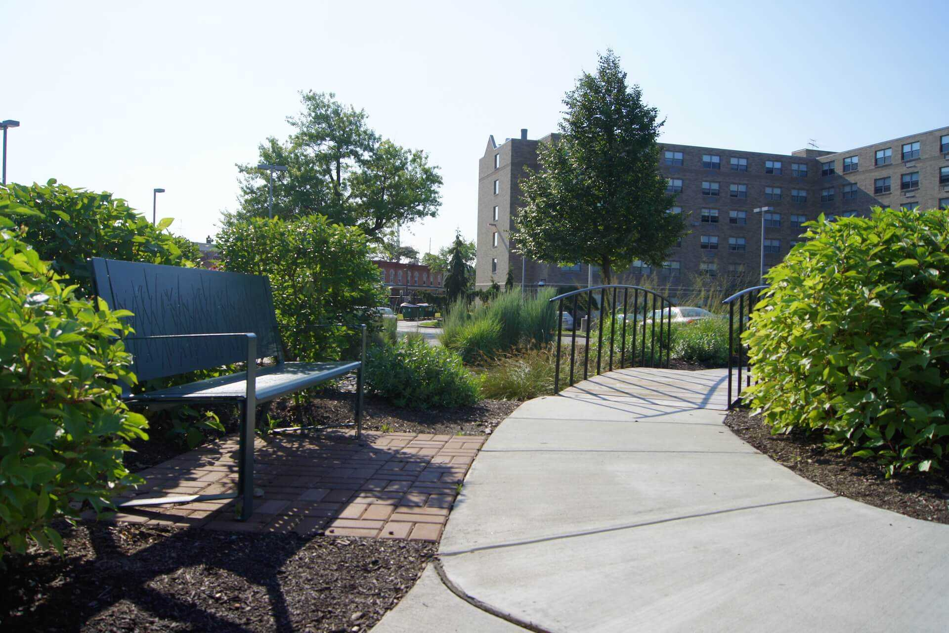 Chair next to the pathway close to small park bridge