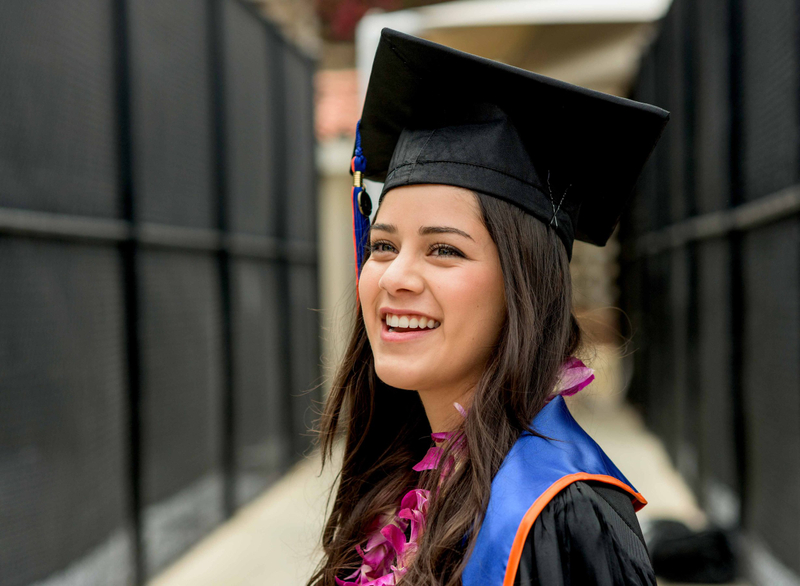 A Pepperdine University graduate smiles for a photo in her cap and gown