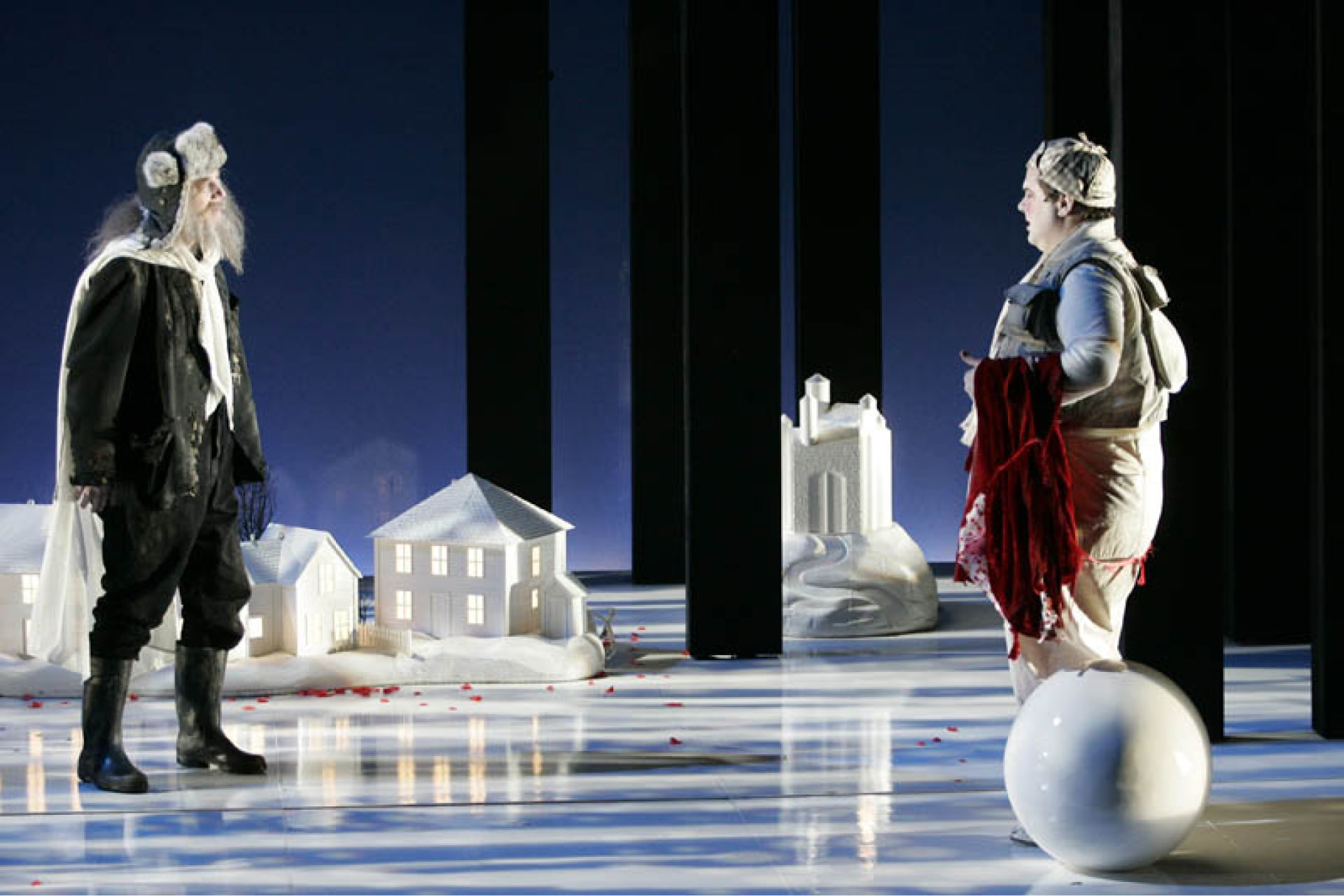 Man in boots and winter hat speak with man in checkered hat carrying red cloak, amongst model houses on white stage.