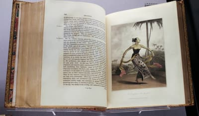 A book showcasing a coloured illustration of a dancing woman in traditional garb.