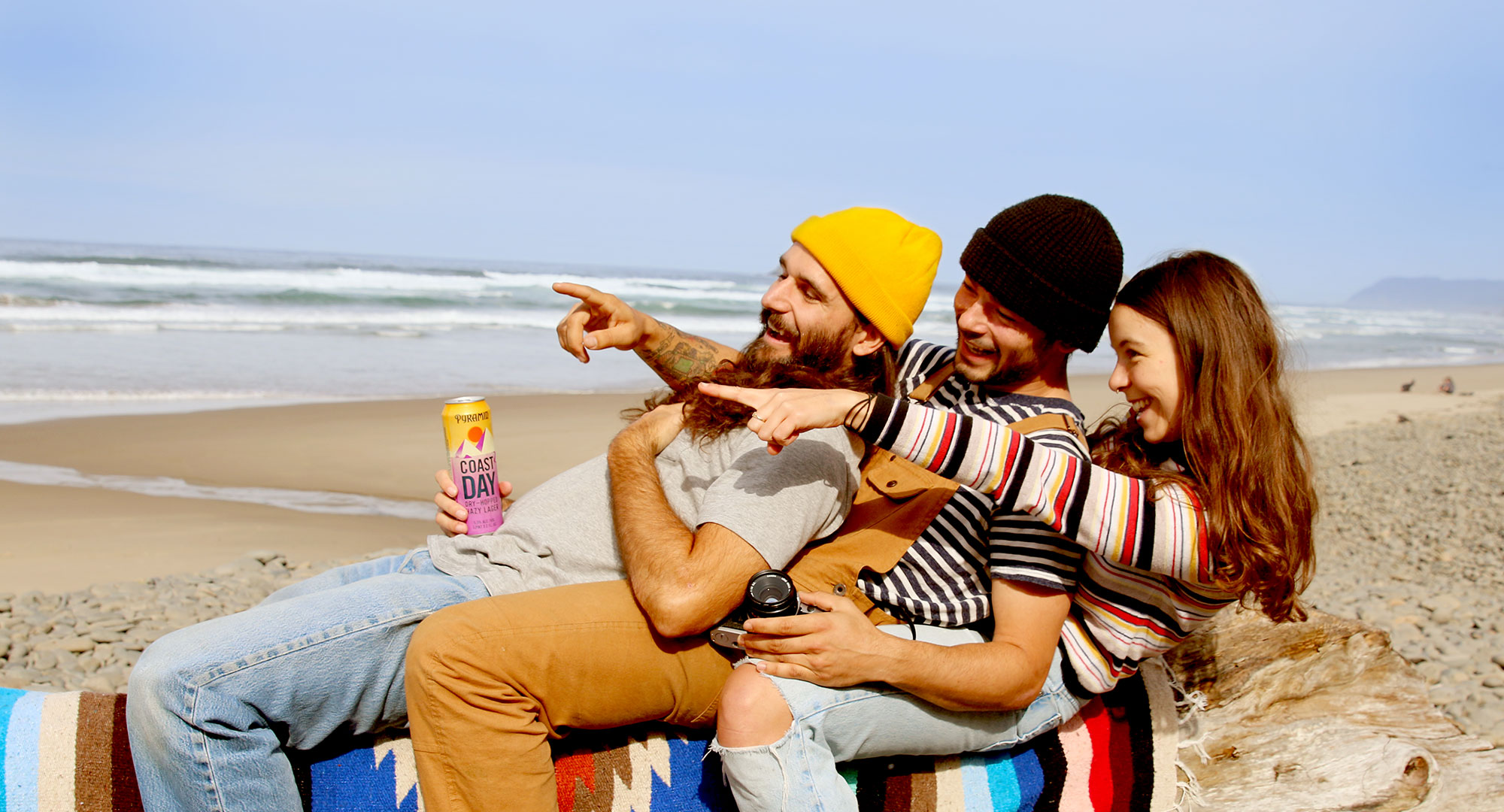 Three friends on a log at the beach