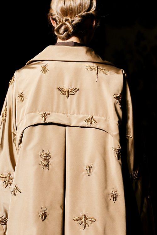 Papillons brodés sur un trench-coat