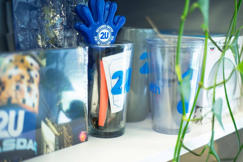 A close up view of various 2U promotional giveaways on a shelf