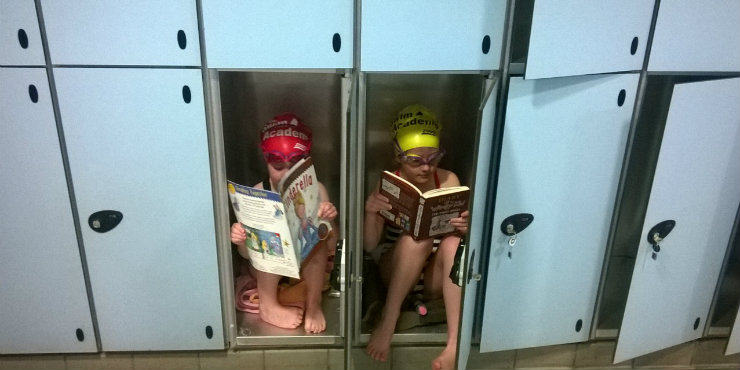 Two young library users enjoying their books in the lockers at Haverhill Swimming Pool