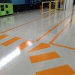Segnaletica orizzontale per il camminamento dei pedoni, integrata nella superficie resinosa di un'industria metalmeccanica.