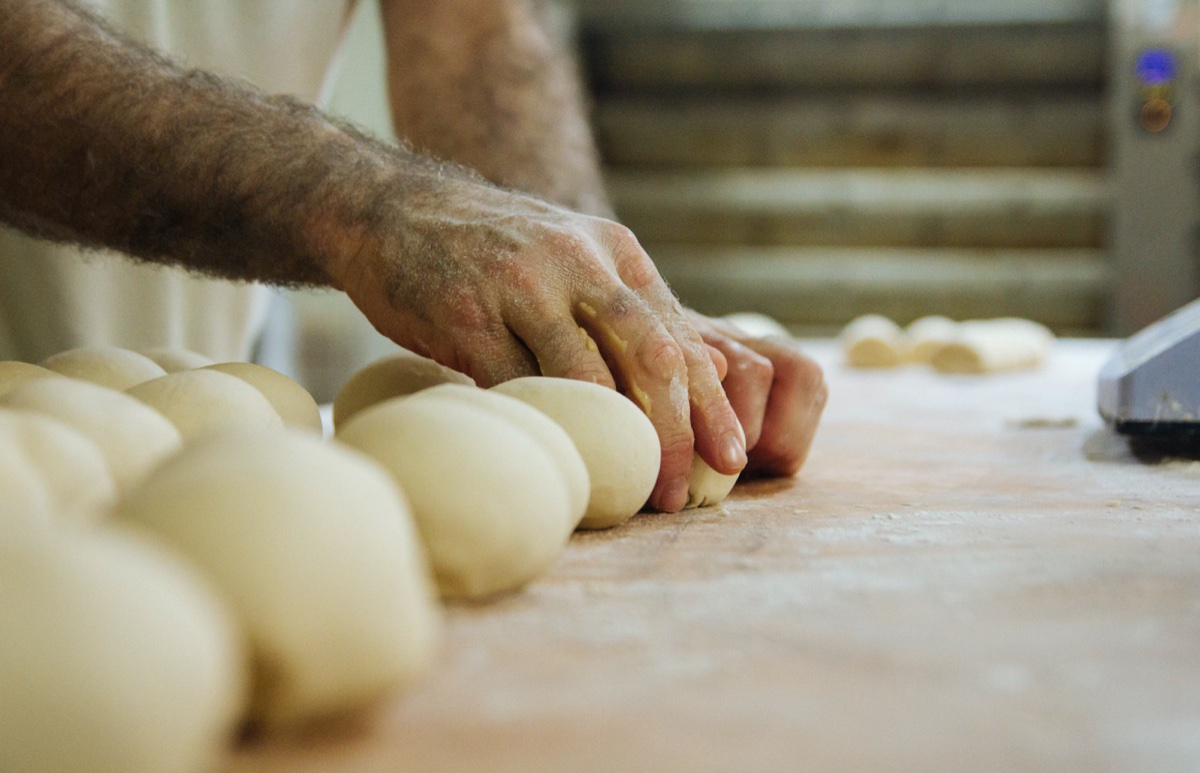 Baker's hands shaping rounds of bread dough .
