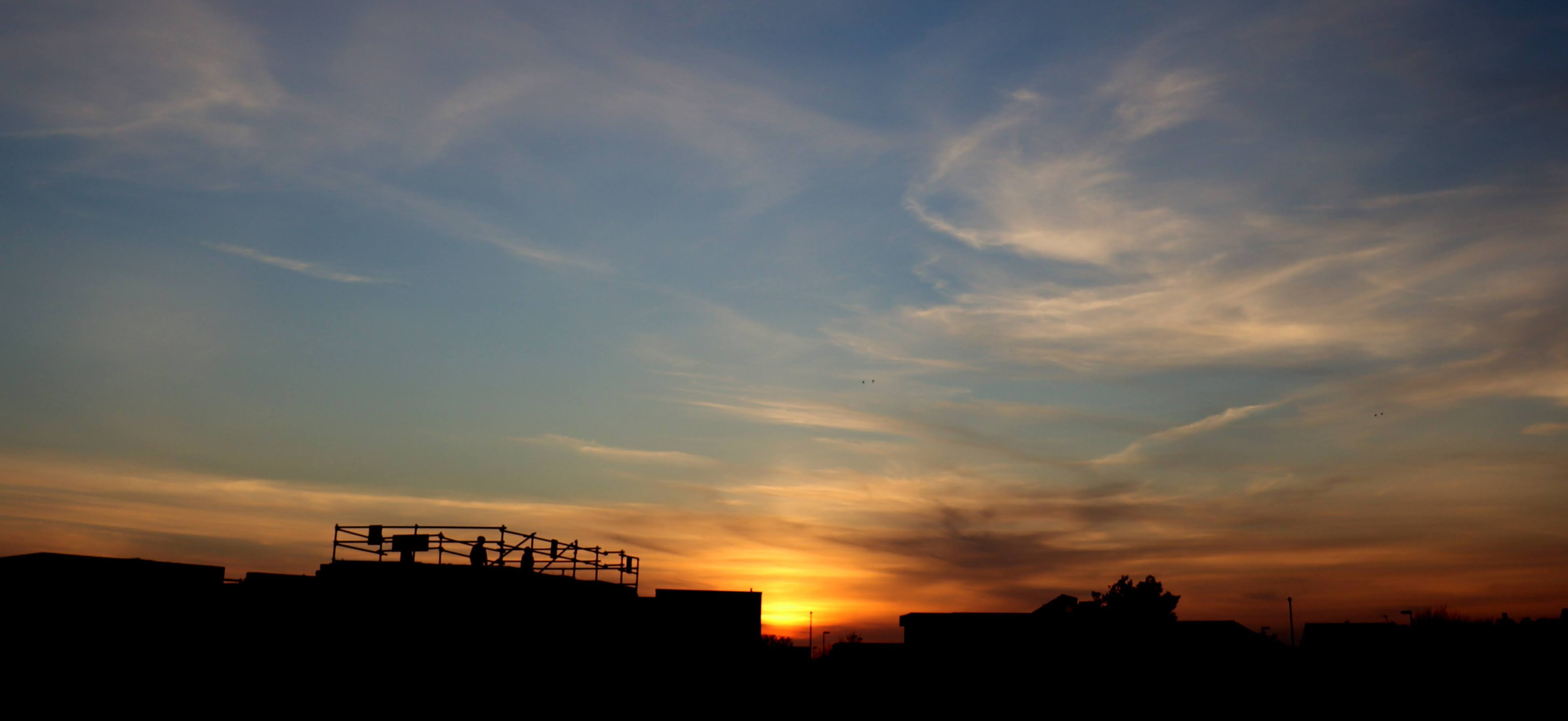 Silhouette of Shoreham fort and rooftops in front of a low red sunset with white clouds above.