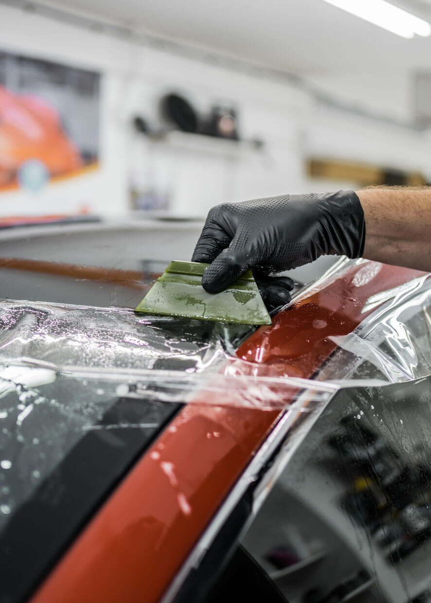 Paint protection film being applied to car