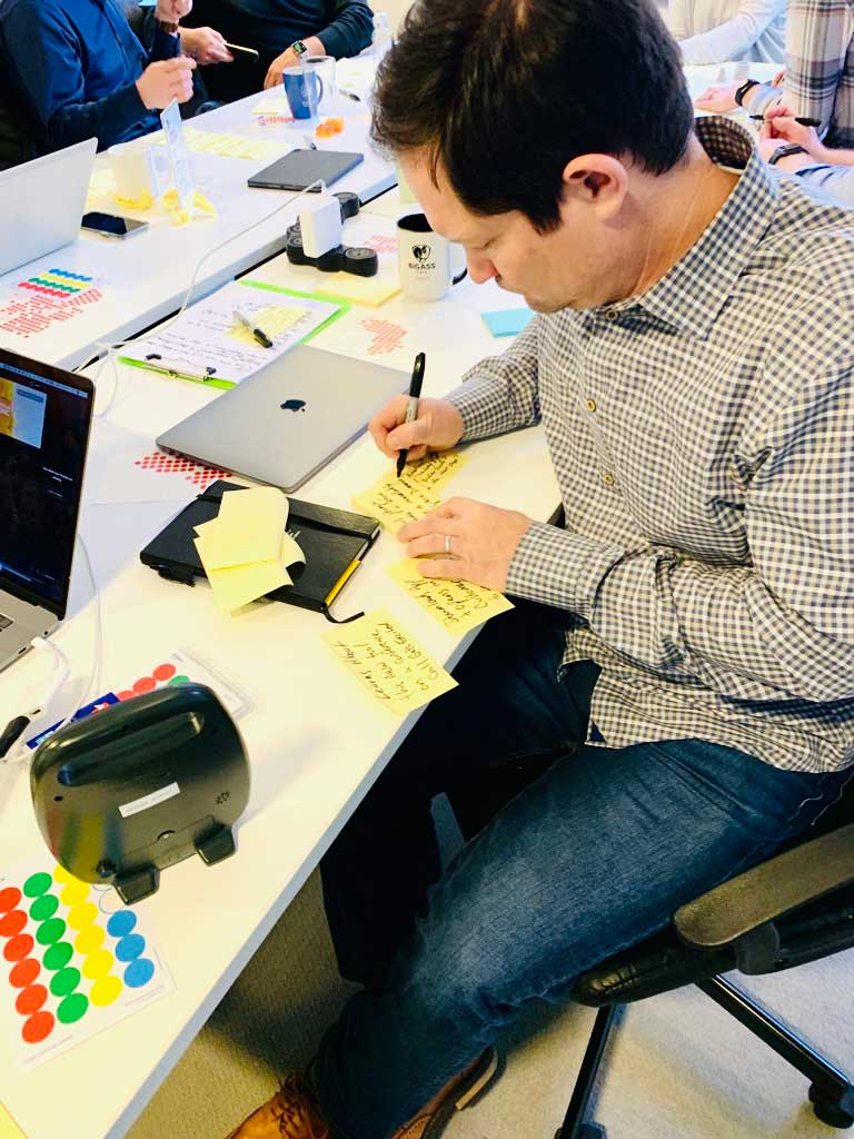 A person writing post-it notes during a Design Sprint