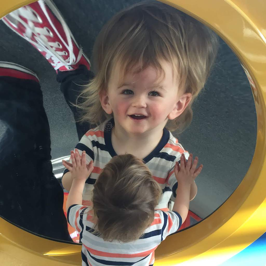 A toddler looks at his distorted reflection in a round mirror.