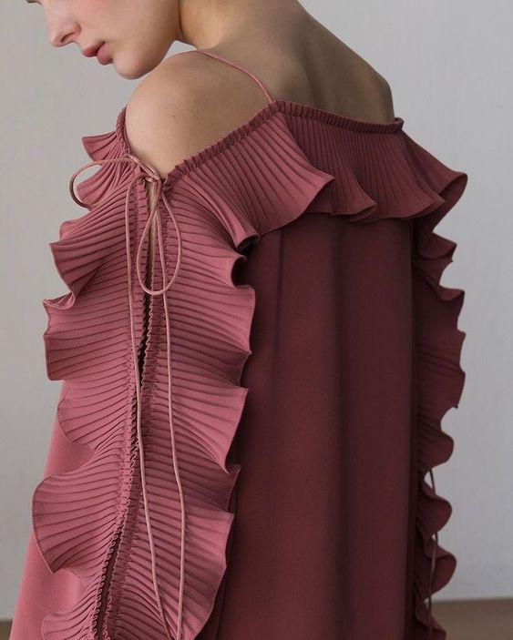 Robe rose ouverte au niveau des épaules avec volants sur les manches