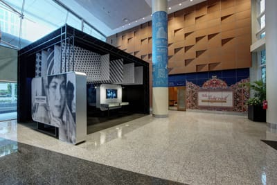 A photo of the Lobby exhibition. A large film still of an actress is on the side of the exhibition. Inside are TV screens showing old movies with there are showcases underneath.