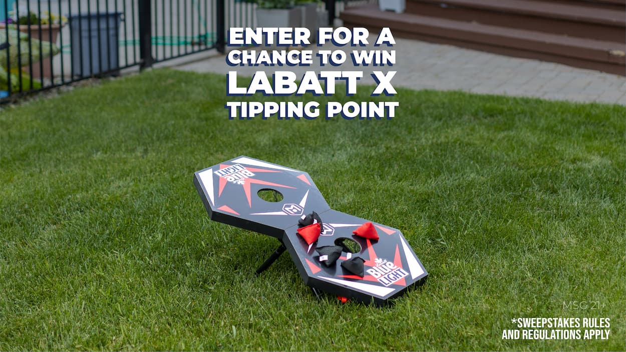 tipping point playing board centered in a lush green lawn, five bean bags already on the board with one shot left to make or break the match