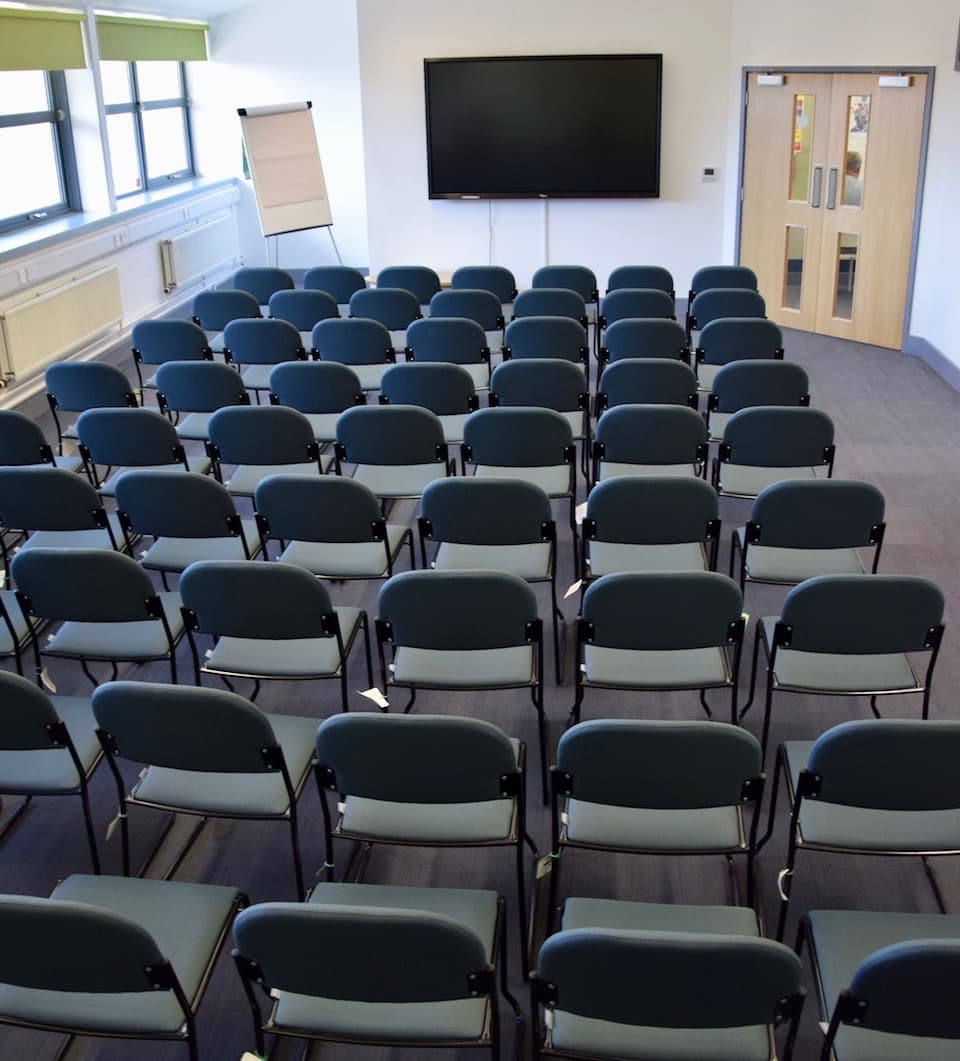Large room chairs set in rows of six in front of a large display screen.