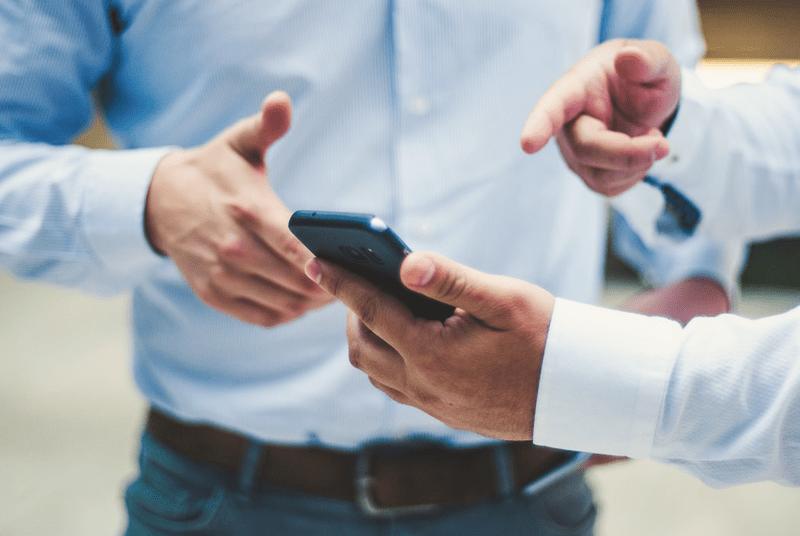 Ausschnitt von zwei Geschäftsleuten, die auf ein Handy zeigen