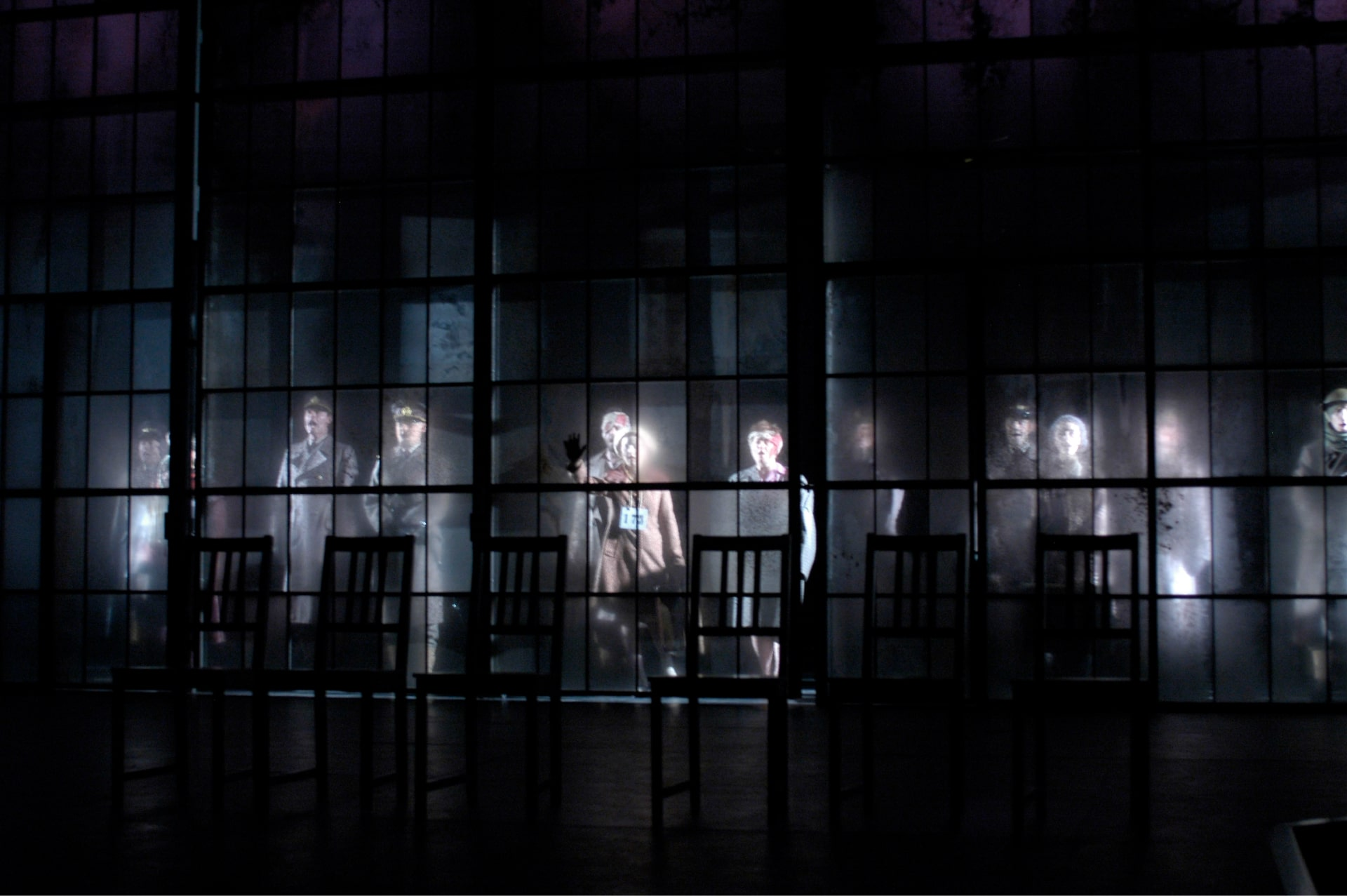 Ghostly figures are lit behind translucent glass wall of windows behind silhouetted empty chairs.