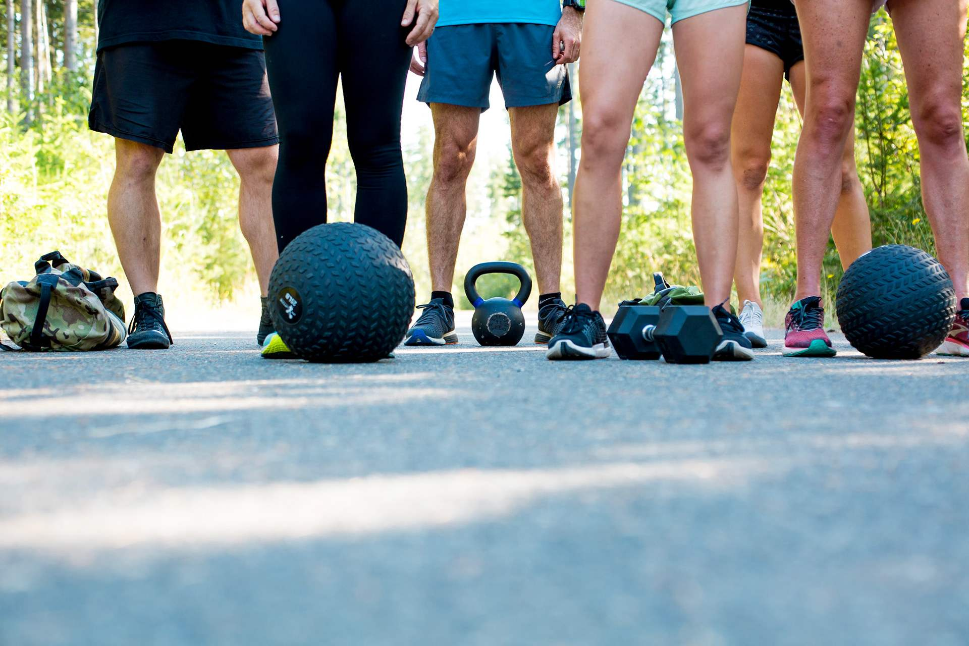 Outdoor fitness class with dumbbells, slam ball, kettlebell