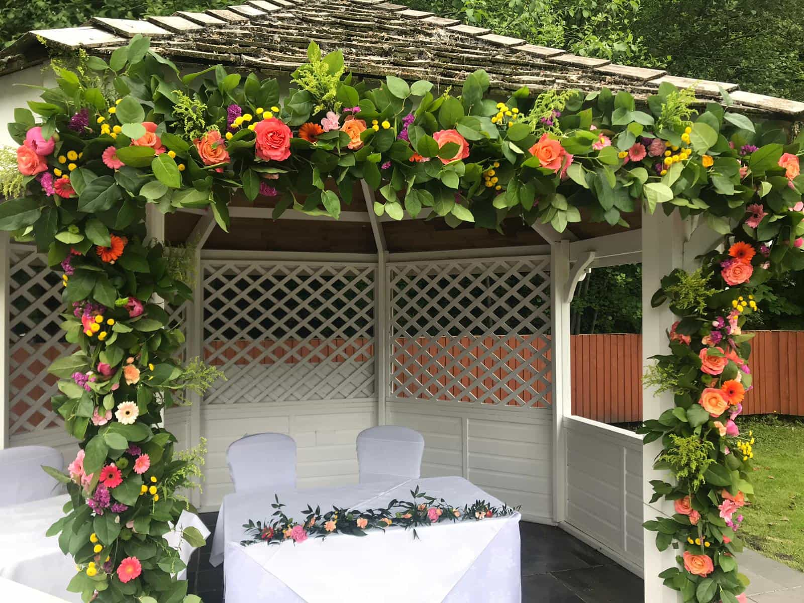 Wedding ceremony outdoor with beautiful floral arch and white seating for bride and groom