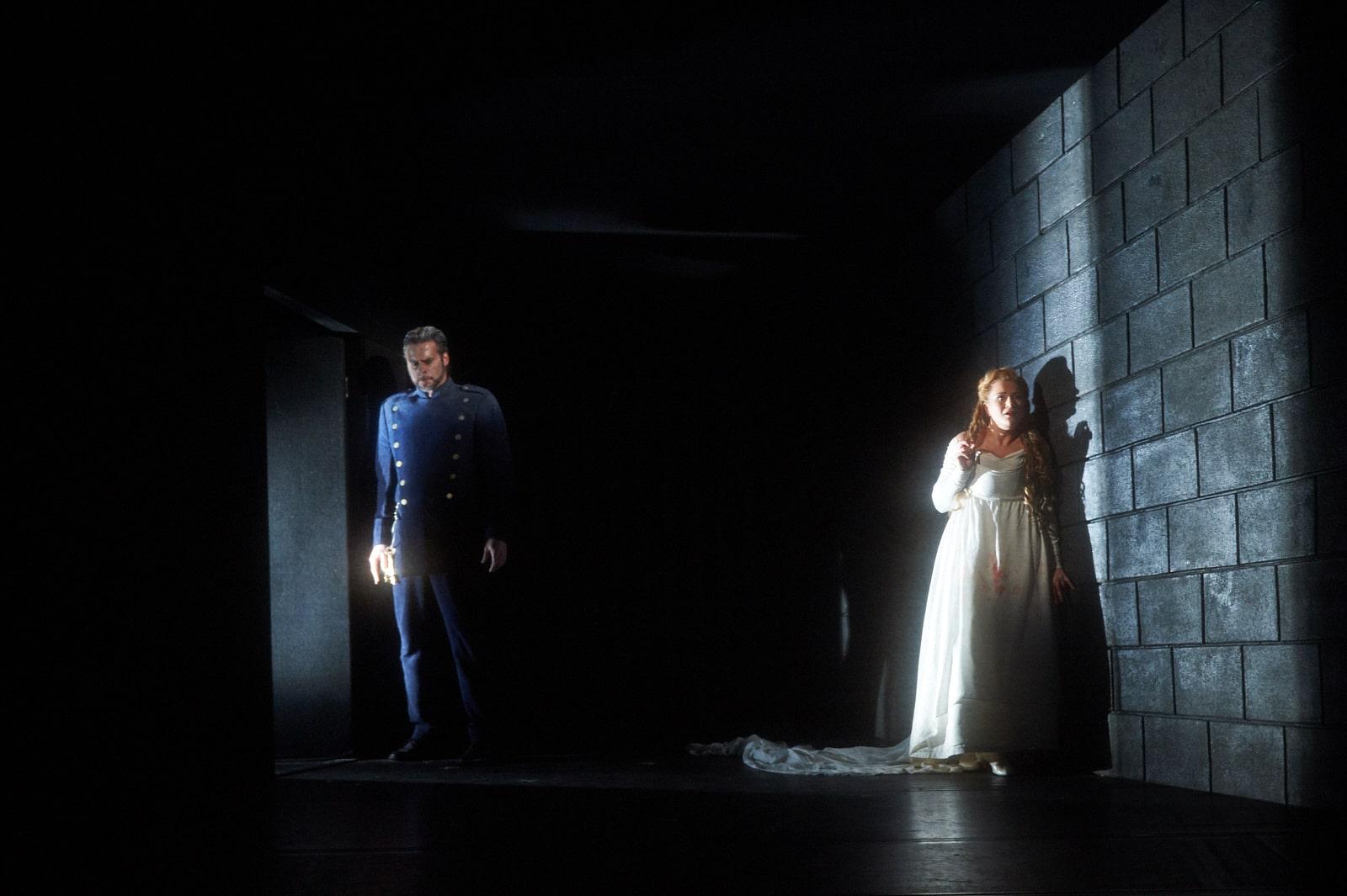 Bride leans against dark brick wall as blue uniformed man broods in doorway lit by shaft of light.