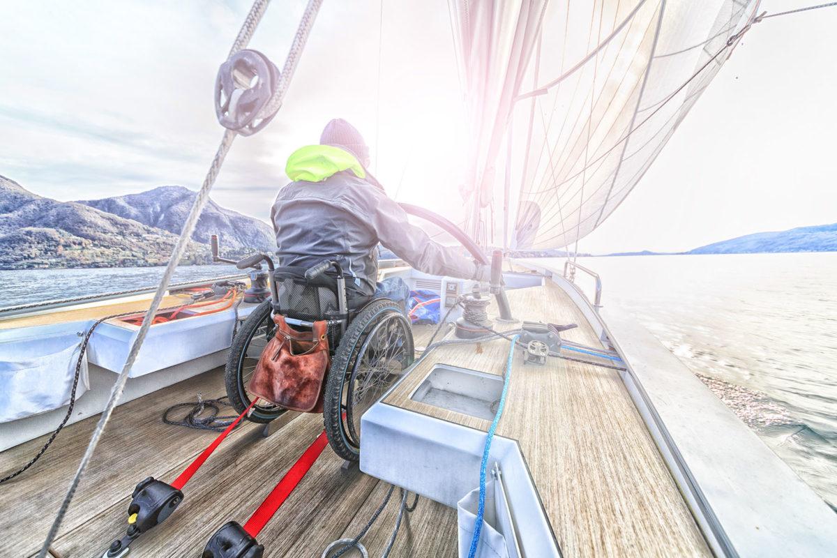 Man in wheelchair sailing in a sailboat
