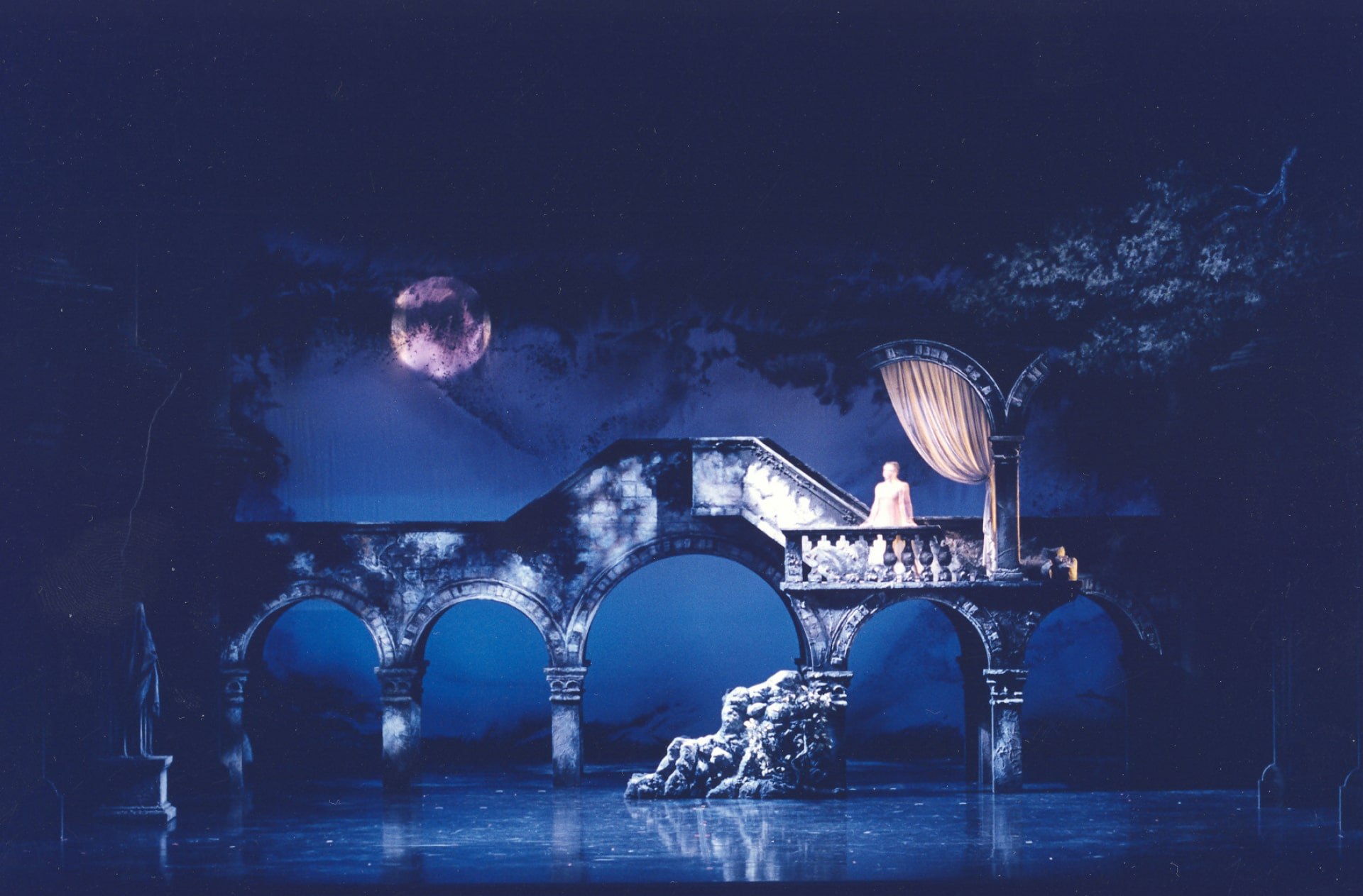 Ballerina in pale dress stands at balcony railing under swagged curtain against bridge and moonlit sky.