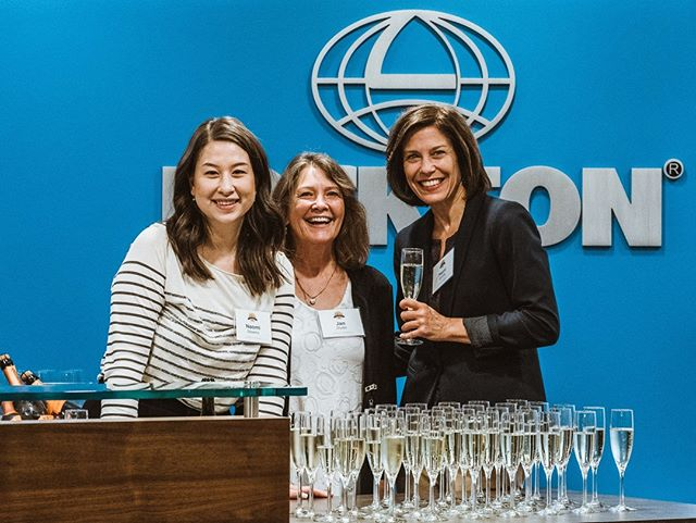 Three Women with champage glasses posing for Camera in front of Lockton Logo