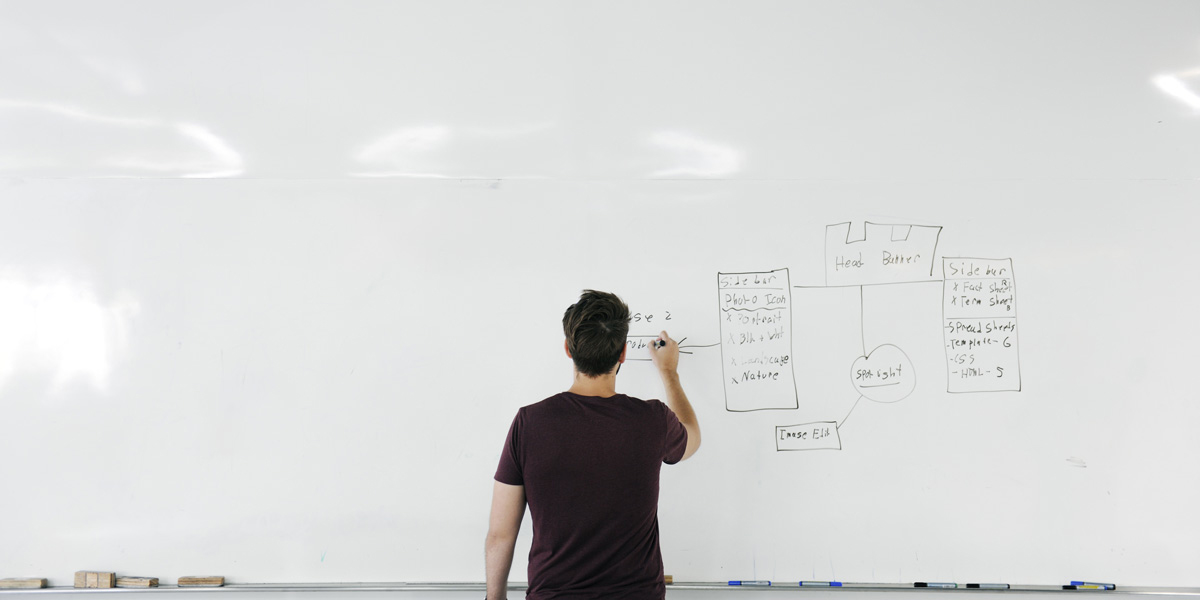 A newly qualified UX designer drawing on a whiteboard