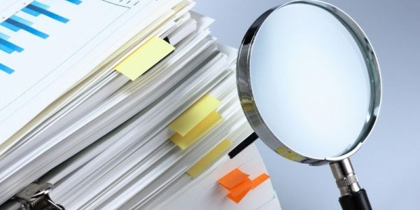 A stack of documents with labels, next to them is a magnifying glass.