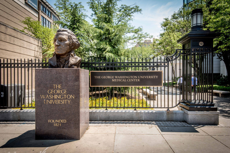 A bust of George Washington along a black metal fence at the entrance to the GWU Medical Center