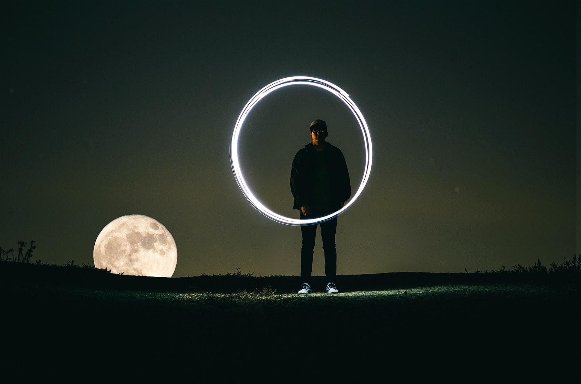 Man in the dark, painting a circle with light and long camera exposure