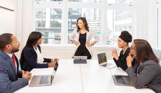 Trainerin mit Kursteilnehmern und Laptops während einer Firmenschulung