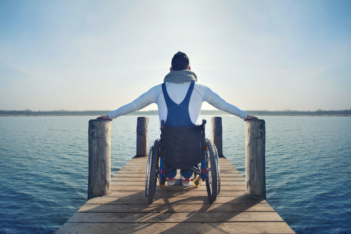 Person in wheelchair on a pier overlooking a large body of water