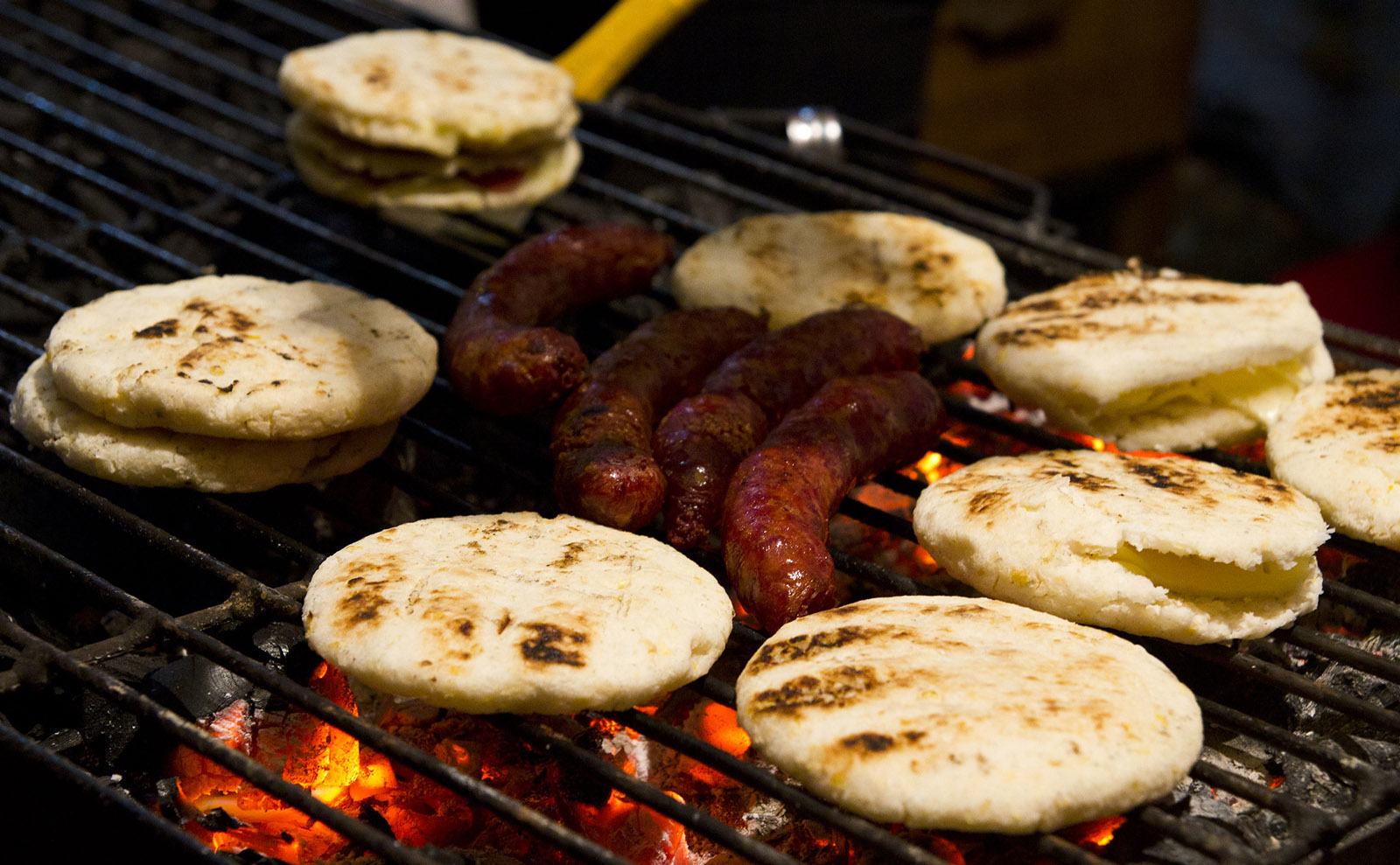 arepas and chorizo on a grill
