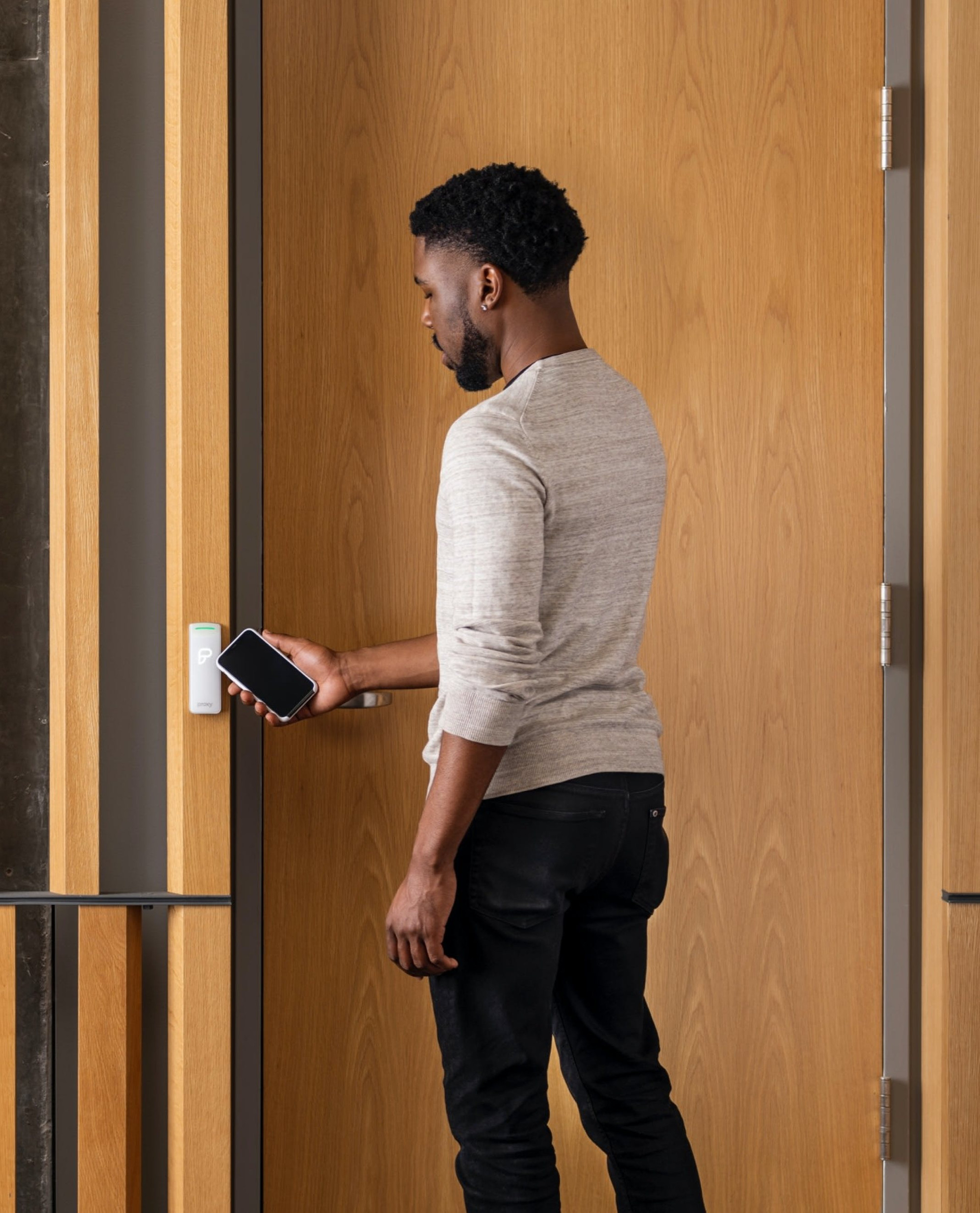 Man tapping his phone on a door reader to open it