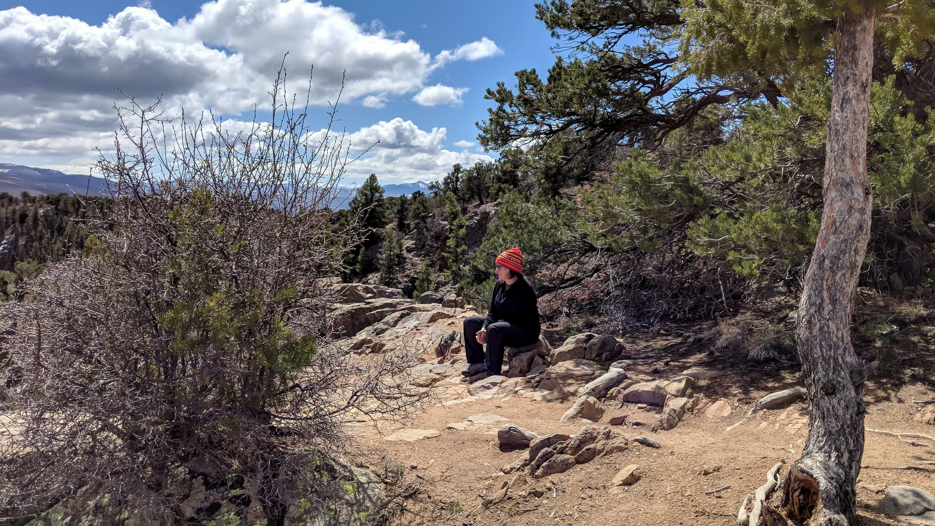 A color photograph of Len sitting on a rock just outside of a pine and juniper forest. She is dressed completely in black except for a shockingly bright orange hat.