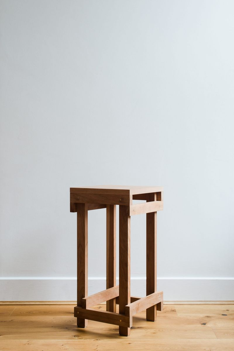 Detailed view of the bespoke solid cherry, felt and brass stool and furniture designed by From Works at the National Justice Museum in Nottingham.