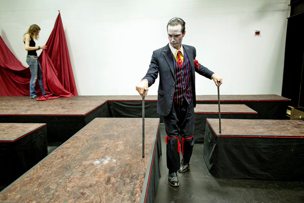 A man in a 3 piece suit and white stage facial makeup peruses a theater set with two walking sticks.