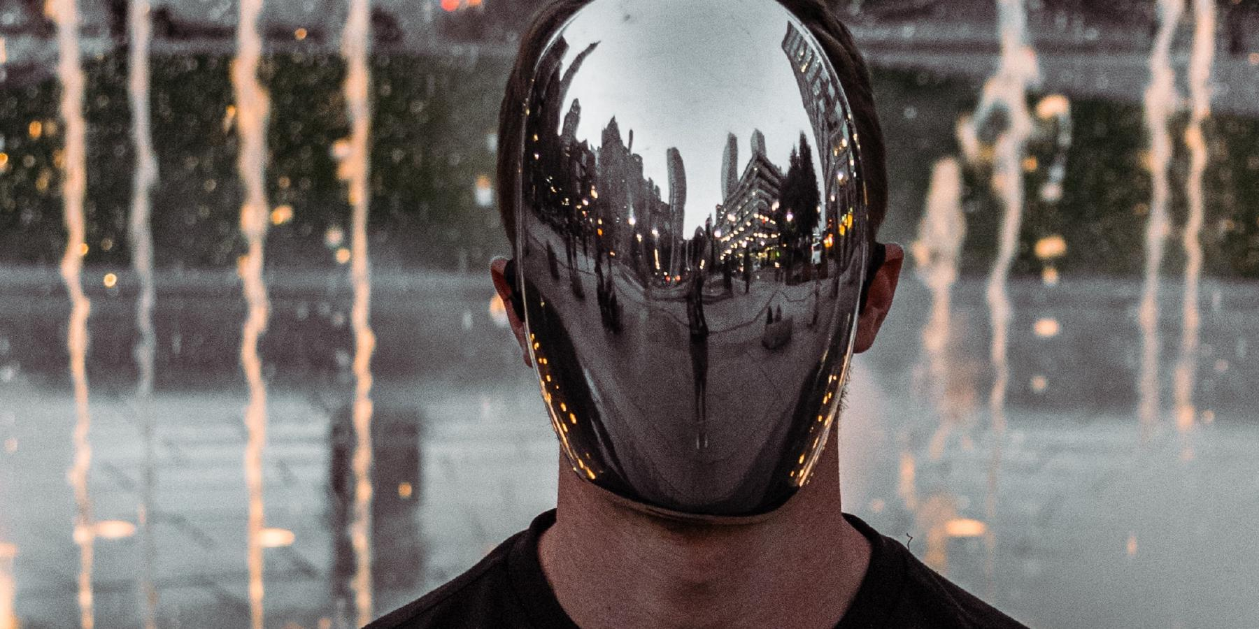 A man wearing a reflective, faceless mask