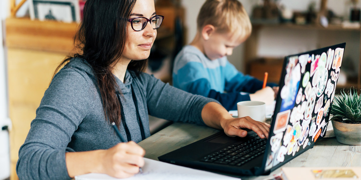 A woman working on a laptop with a child sitting next to her