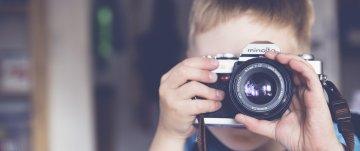 Menino tirando foto com câmera fotográfica