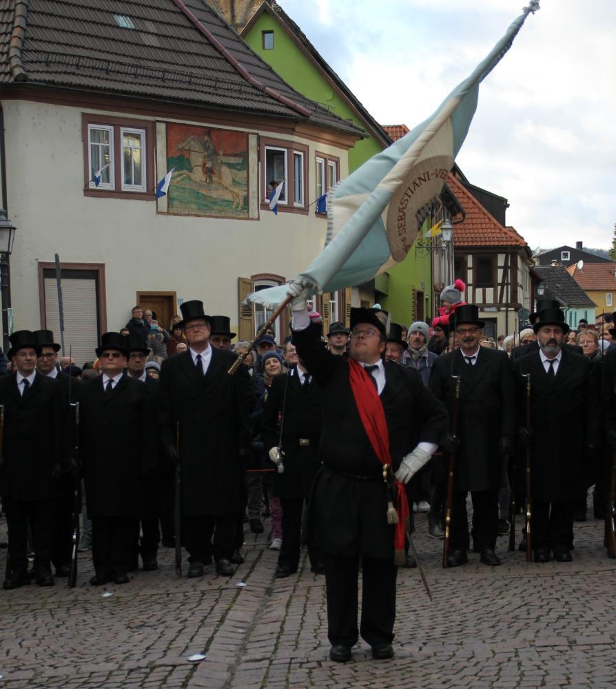 """Der Fähnrich trägt die Vereinsfahne. Er steckt diese jeweils in der Kirche und an der Dreifaltigkeitssäule auf. Außerdem schwenkt er die Fahne auf dem Marktplatz zu dem Musikstück """"Über den Wellen"""", dem Höhepunkt des Festes."""