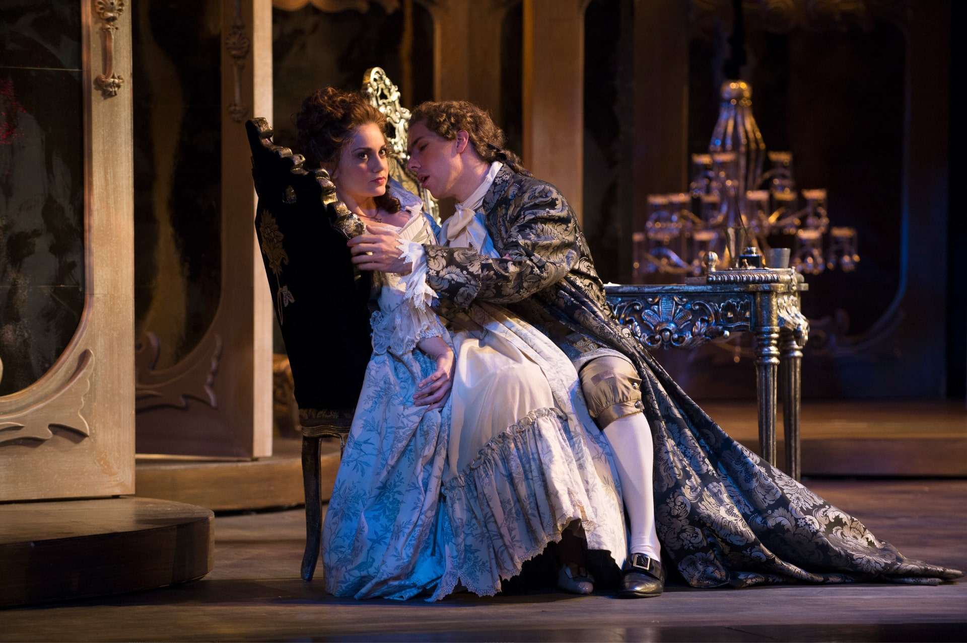 Man in brocade frock coat embraces bored woman in pleated white gown seated on desk chair.