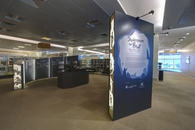 A photo of the main exhibition. The First Folio lies in the showcase in the middle, surrounded by informational walls.