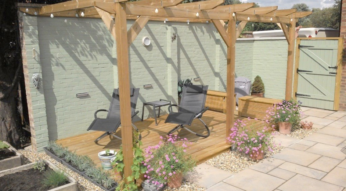 A medium-sized lean-to pergola over some decking, strung with decorative lights and surrounded by assorted potted flowers.