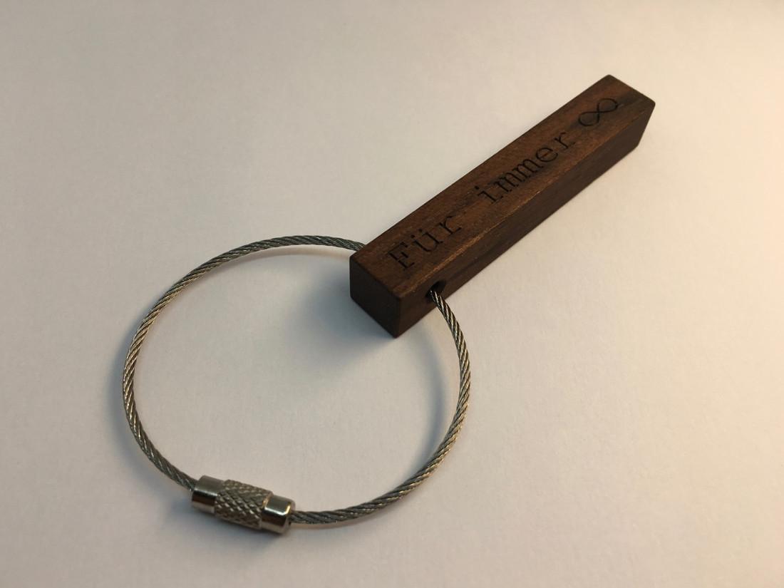Die Schlüsselanhänger sind wahlweise in dunklem Nussbaumholz oder in hellem Eichenholz erhältlich.