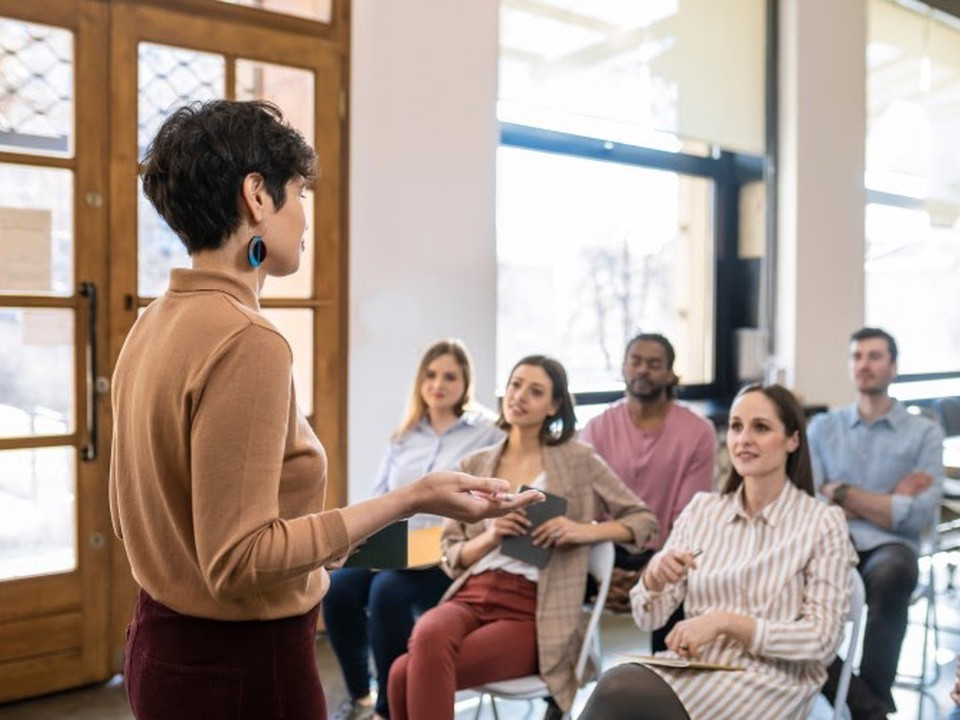 A school administrator presents to a group of teachers sitting in chairs.