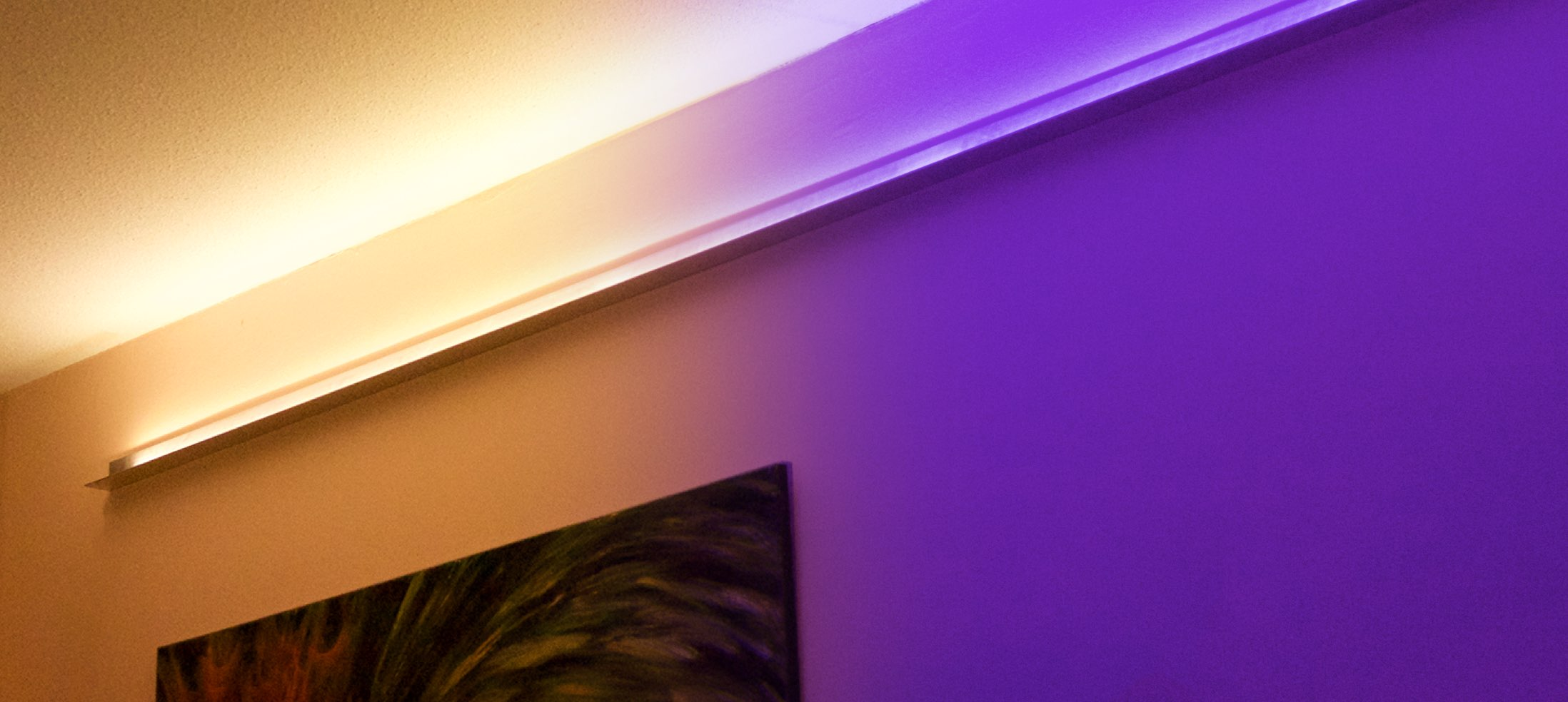 Strip of LED lights on wall shown in different colours