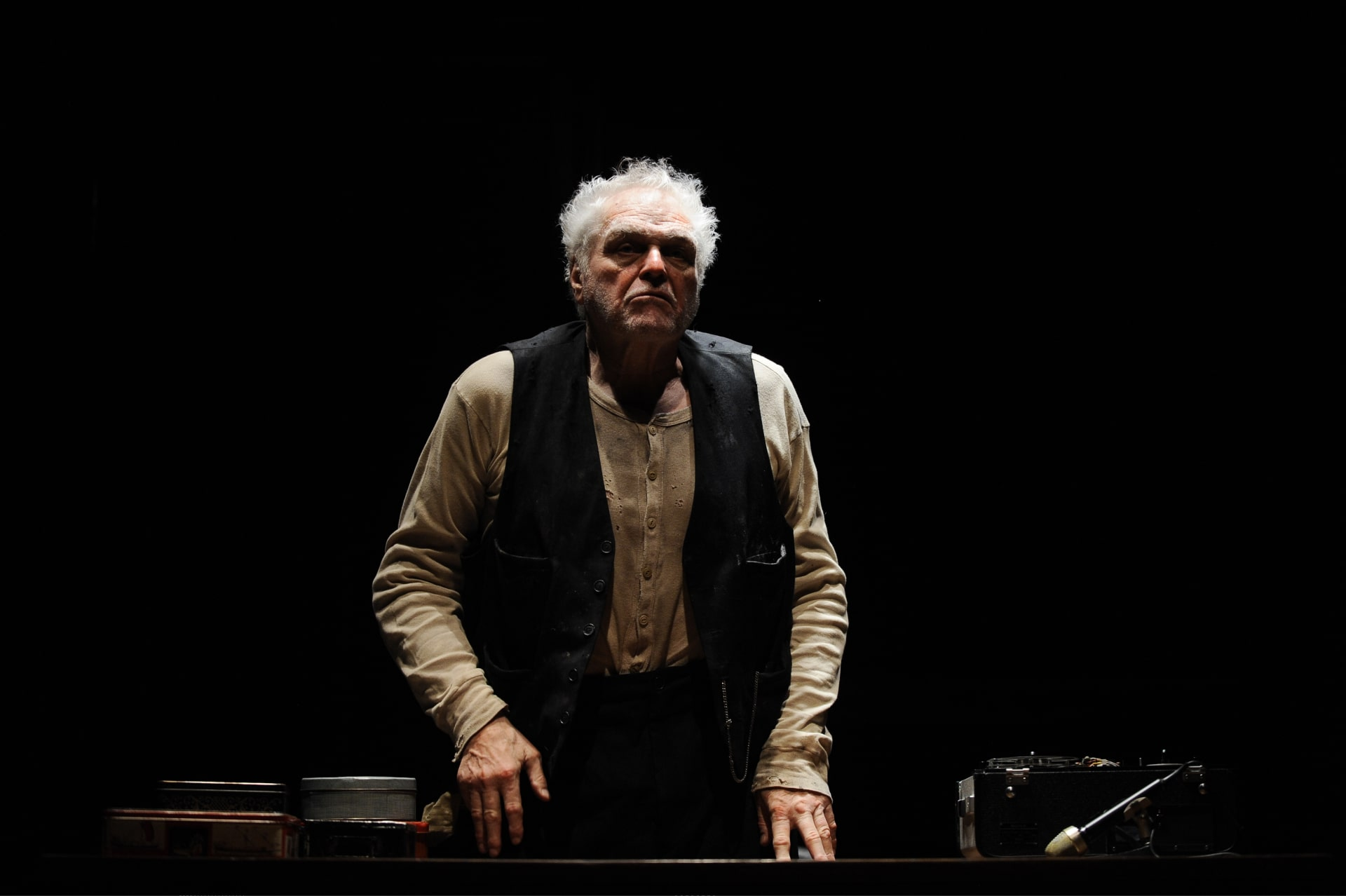 Scuffy older man in waistcoat stands fingers poised on desk under bright light.