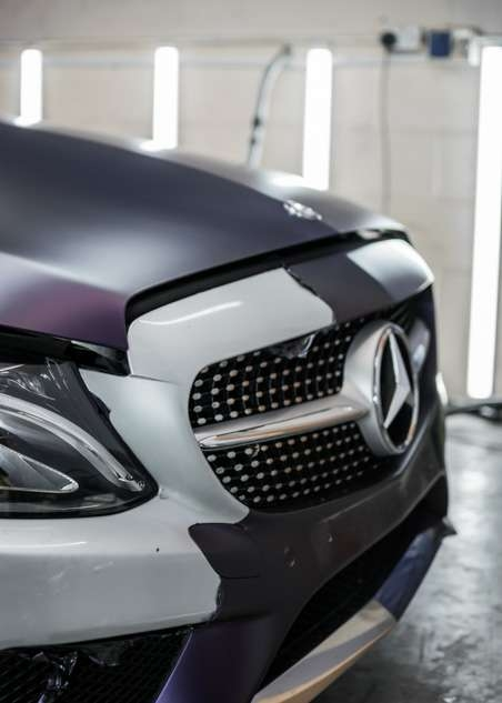 Purple vinyl wrap being removed from car grey Mercedes C Class